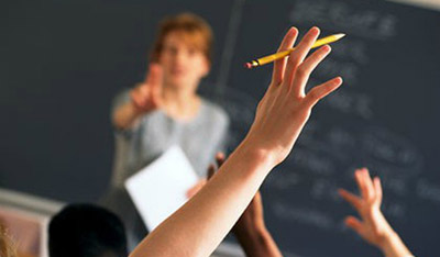a student's hand raised while a teacher is lecturing